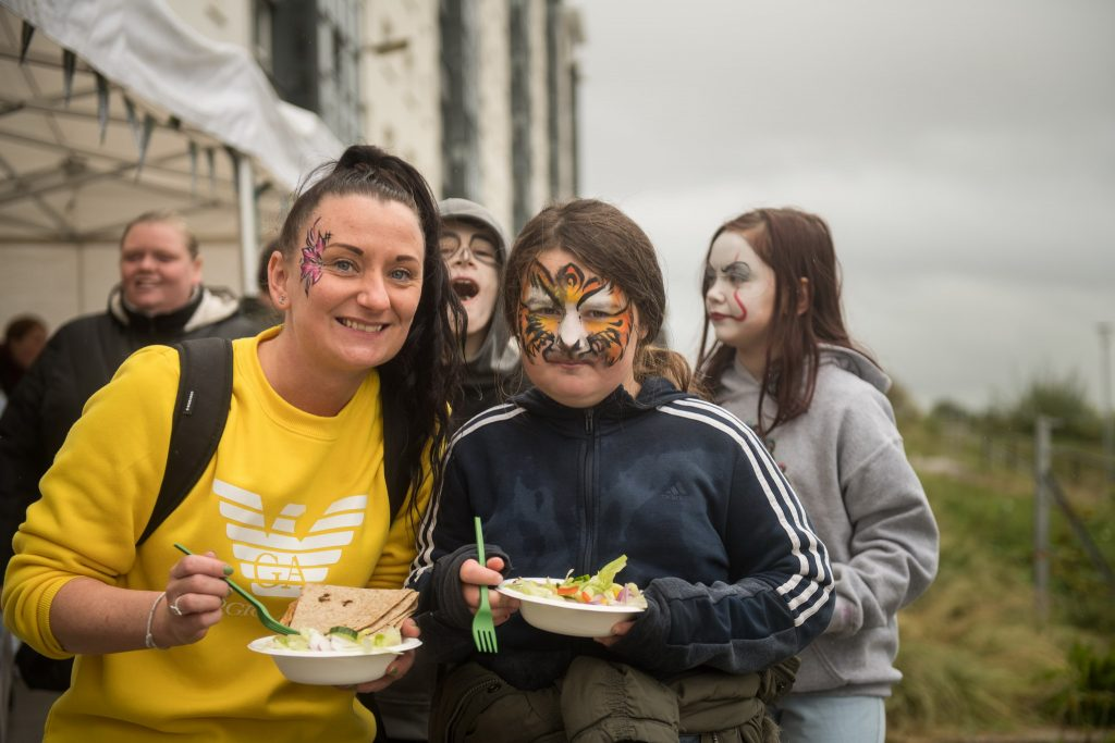 Photograph of members of the Cardonald community (child with face-paint and woman, with children in background) at Halfway Community Park at Moss Height Avenue, to celebrate its opening.